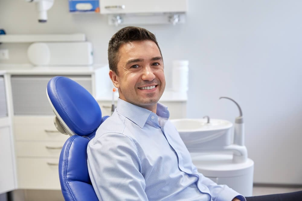 male sitting in dental chair, smiling